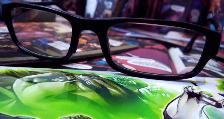 Óculos disposto sobre várias revistas em quadrinhos.