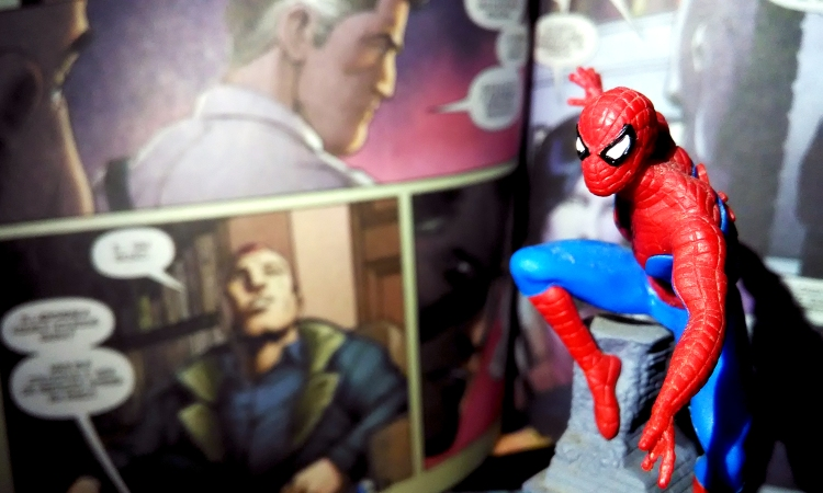 Figura do Homem-aranha em primeiro plano, tendo ao fundo páginas de história em quadrinhos