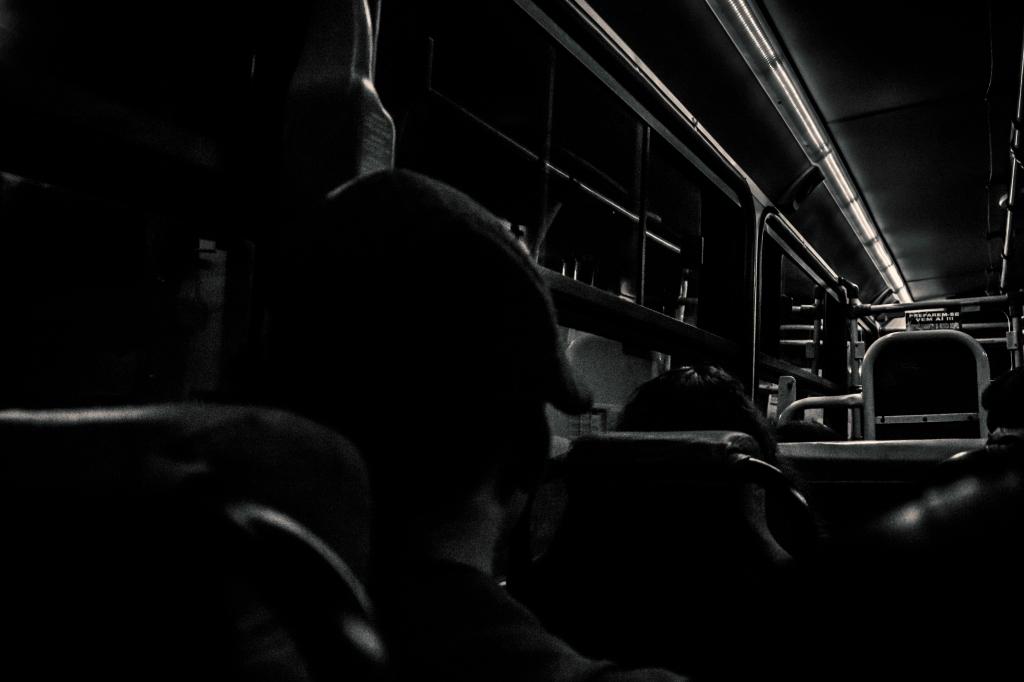Ônibus escuro, silhuetas de pessoas